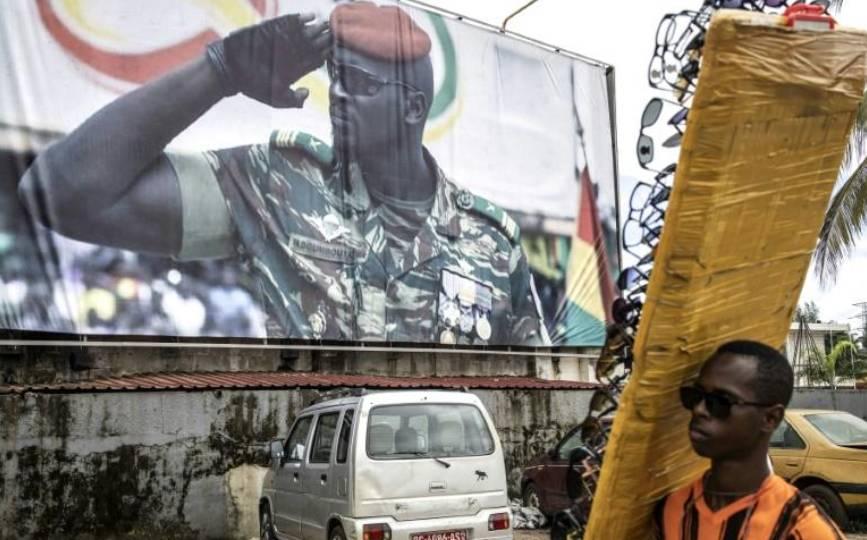 Un vendeur de lunettes passe devant une affiche géante montrant le chef de la junte guinéenne, le lieutenant-colonel Mamady Doumbouya, à l'origine du putsch contre le président Alpha Condé, à Conakry le 11 septembre 2021. afp.com - JOHN WESSELS
