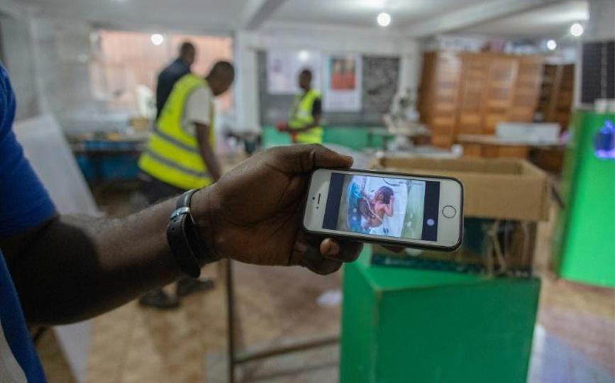 Un technicien de l'Agence universitaire pour l'innovation (AIU) surveille, à l'aide d'un téléphone portable, un bébé placé dans une couveuse à Bafoussam, au Cameroun, le 20 septembre 2021 afp.com - Daniel Beloumou Olomo